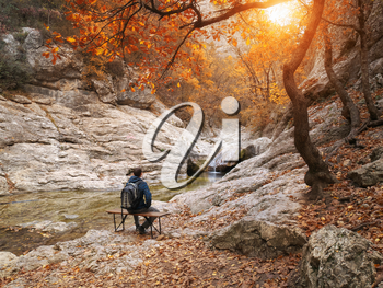 Man sitting on autumn canyon. Relax and emotional scene.