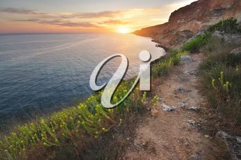 Footpath in mountains above the sea at sunset. Scenic landscape