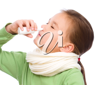 Cute girl spraying her nose with nasal spray, isolated over white