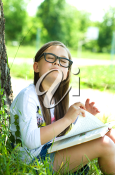 Cute little girl is reading a book outdoors