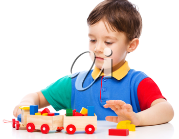 Cute little boy is playing with building blocks, isolated over white