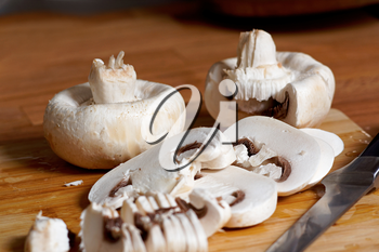 Whole and sliced white mushrooms in kitchen on wooden Board