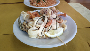 Fish Assorted deep-fried on plate in rustic restaurant of Italy. Shrimps, squid, octopus