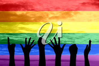 Silhouette of hands of people the gay parade and the LGBT movement on the background of rainbow flag