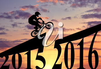 Concept of the new year. Extreme cyclist makes a jump between 2015 and 2016 years at sunset