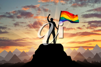 Silhouette with the gay rainbow flag on a mountain top. Concept rights gays