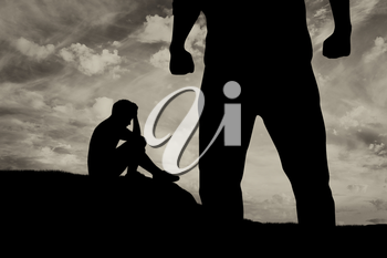 Child abuse and bullying in the family. Silhouette of a crying frightened boy and aggressive father with fists