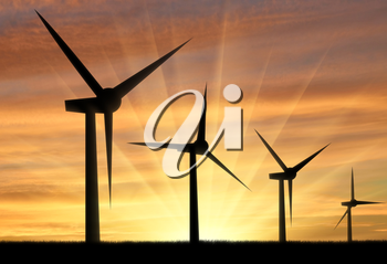 Silhouet a wind generator against a sunset background. Concept of renewable energy