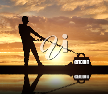 Silhouette of a man chained to a heavy load under the name of the credit. He drags him hard. The concept of credit as a heavy load