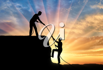 Silhouette of a man helping another man climb up. The concept of teamwork and mutual assistance