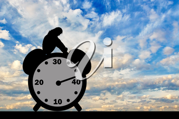 Sad woman sitting on the clock where the arrow shows almost 40 years. Conceptual image of impending menopause in women