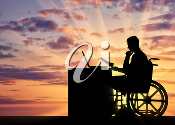 Silhouette of a man a businessman disabled in a wheelchair sitting at a table. The concept of working disabled people