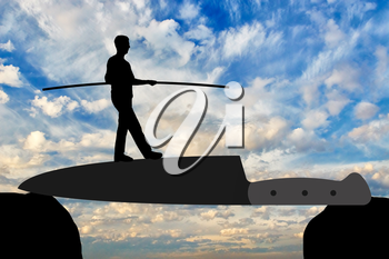 Silhouette of a man walking on a knife blade balances. Concept of strength and determination in business