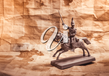 Figurine soldier on a horse on the background of old paper.