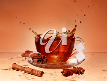 Cup of tea on glass with orange background