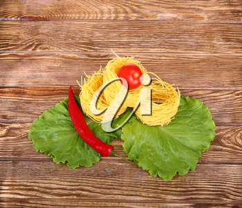 Pasta on the wooden background with tomato, pepper lettuce and pepper