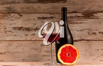 Red wine in glass with bottle and grapefruit on wooden background