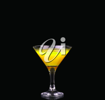 Yellow cocktail in martini glass isolated on black background
