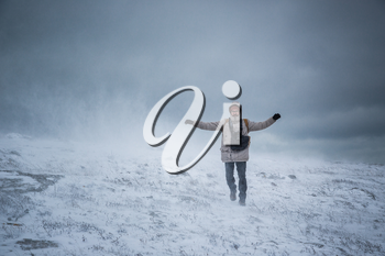 Wintery scene of shivering man in snowstorm or ice storm. Man walking in the snowstorm in the mountains