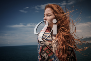 Gorgeous Romantic Girl Outdoors. Beautiful Model near sea. Long Hair Blowing in the Wind. Red-haired girl in ethnic costume on the ocean coast