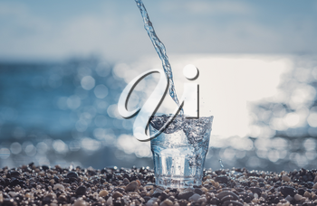 splashing water in a glass by the sea. Beautiful glass with ice and pure mineral water