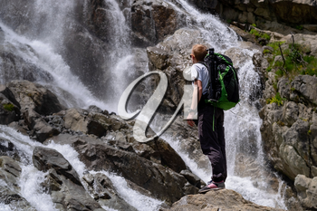Man hiking with backpack looking at waterfall. Travel Lifestyle adventure concept, active vacations into the wild harmony with nature. North Caucasus, Dombai, Russia.