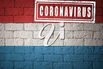 Flag of the Luxembourg with original proportions. stamped of Coronavirus. brick wall texture. Corona virus concept. On the verge of a COVID-19 or 2019-nCoV Pandemic.