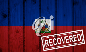 flag of Haiti that survived or recovered from the infections of corona virus epidemic or coronavirus. Grunge flag with stamp Recovered