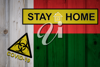 Flag of the Madagascar in original proportions. Quarantine and isolation - Stay at home. flag with biohazard symbol and inscription COVID-19.