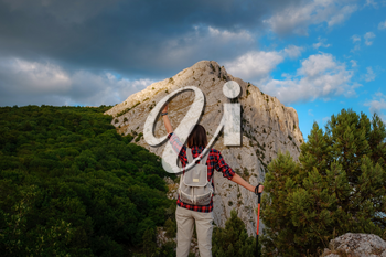 Fit female hiker with backpack and poles standing with raised hands on a rocky mountain ridge and peaks in a healthy outdoors lifestyle concept