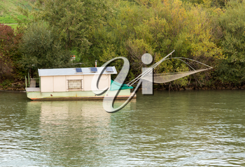 Small houseboat on side of River Danube used for fishing near Vienna, Austria