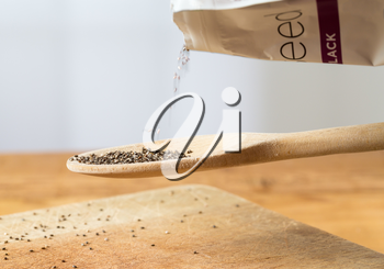 Superfood known as black chia seeds are poured from packet into a wooden backing spoon over wood bread board on kitchen table