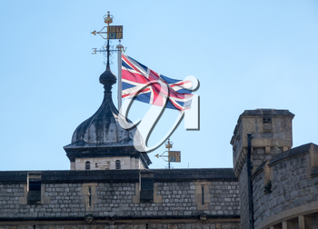 Union Flag rises above the walls of the Tower in London, England, UK