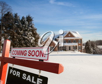 For Sale and Coming Soon realtor sign in front of large brick single family house in expansive snow cover yard in mid winter