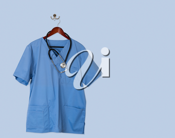 Blue medical scrubs uniform shirt hanging on a hanger with stethoscope and on hanger and hook on blue wall ready for work