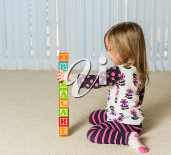Young female toddler knocking down a tower of wooden blocks at home spelling Obamacare