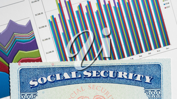Social Security card in the USA laid on top of charts and graphs of budget in retirement