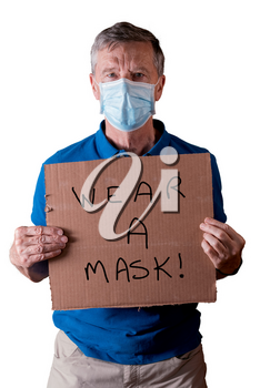 Senior caucasian man holding a blank cardboard sign saying wear a mask. He is isolated against a white background