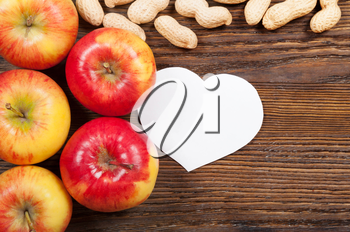 Ripe red apples and peanuts on a wooden background. Top view. Vegan concept.