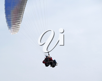 Paraglider is flying in the blue sky