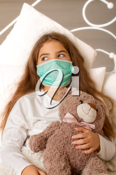 A little girl with her favorite toy bear is lying sick in bed with a gauze bandage over her face.