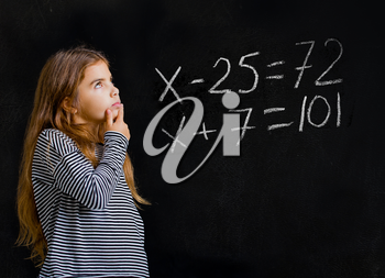 a little girl is standing near a school board and is trying to solve a difficult task for her in mathematics