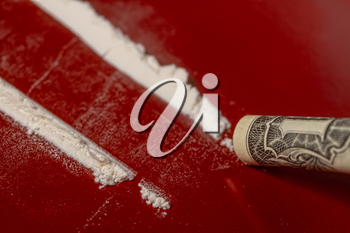 plastic card, cocaine poured in tracks and a one-dollar bill rolled up into a tube for taking the drug on a dark red surface close-up