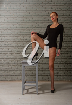young sexy girl with wet red hair in a black sports bodysuit and mesh pantyhose on a rough wooden stool against a gray brick wall