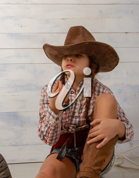 A little girl in a wide-brimmed cowboy hat wearing a traditional dress and high boots with a lasso is eating a straw on a light wooden background.