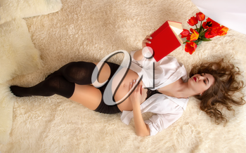 A beautiful young girl in the sixth month of pregnancy is lying on a bright bed in the shirt of her husband with her hair down next to a book and a telephone and a bouquet of tulips.
