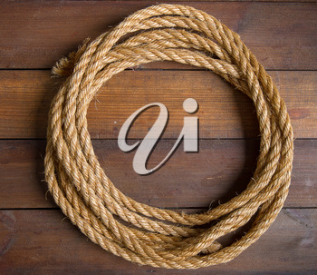 round frame from a skein of coarse rope with place for text on a dark wooden background