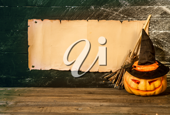 Blank manuscript with place for text witch's broom flying hat and pumpkin on dark background