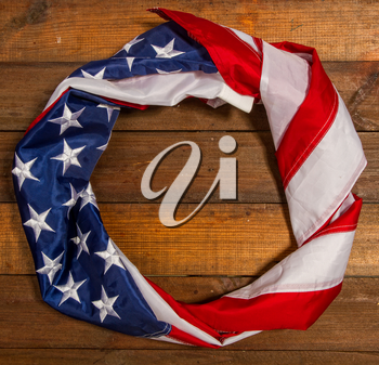 the star-striped flag of the USA lies on a wooden surface rolled into a ring
