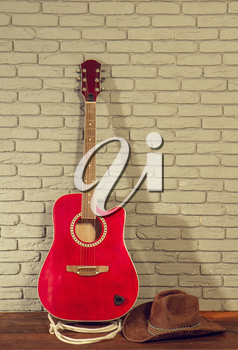 beautiful classical acoustic guitar wide brim cowboy hat and lasso on gray brick background